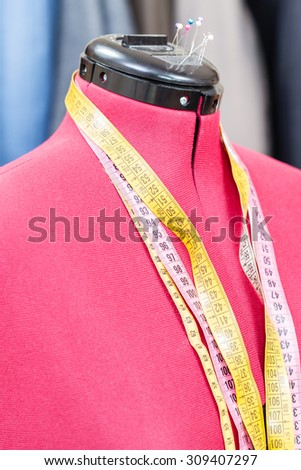 red tailor dummy - mannequin with measure tapes and ready dresses on background - stock photo