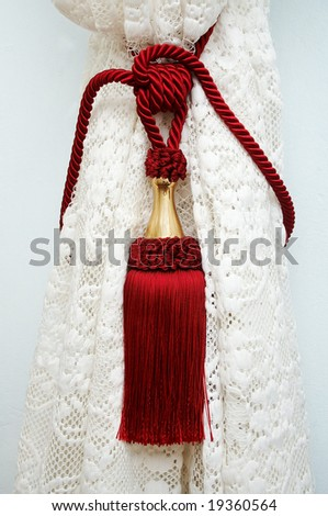 Red tassel on the drapery - stock photo