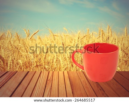 Red tea mug on wooden surface against of golden wheat ears and blue sky. - stock photo
