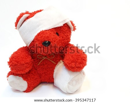 Red teddy bear with bandage over his head and leg with free text space on right - stock photo