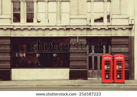 Red telephone booth in street with historical architecture in London. - stock photo