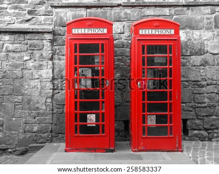 Red telephone box in London over desaturated black and white background - stock photo