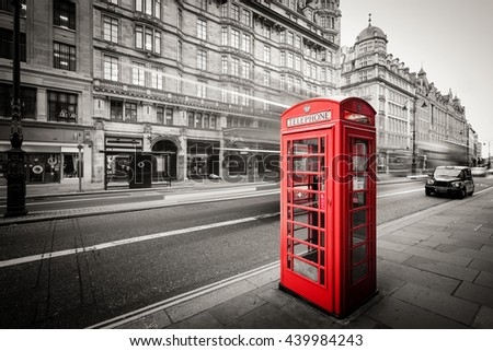 Red telephone box in street with historical architecture in London isolated. - stock photo