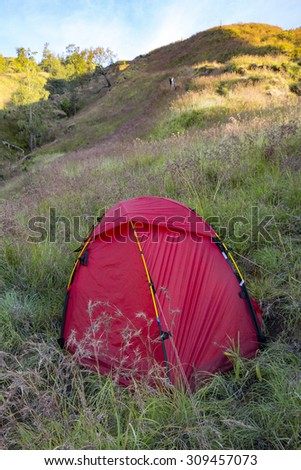 Red tent on top of tropical climate mountain. - stock photo