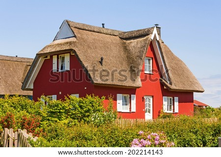 red thatched-roof vacation home with garden - stock photo