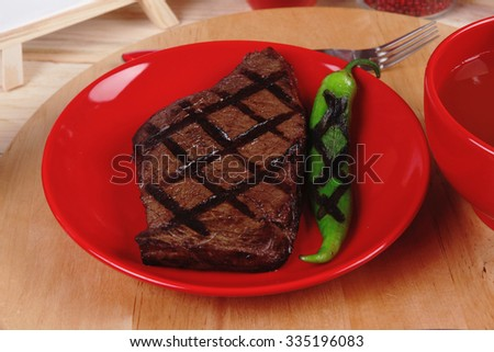 red theme lunch : fresh grilled bbq roast beef steak on red plate with green chili tomato soup ketchup sauce and modern cutlery served on wooden plate over table - stock photo