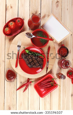 red theme lunch : fresh grilled bbq roast beef steak red plate green chili tomato soup ketchup sauce paprika small glass ground peppercorn modern cutlery served wooden plate empty nameplate menu board - stock photo