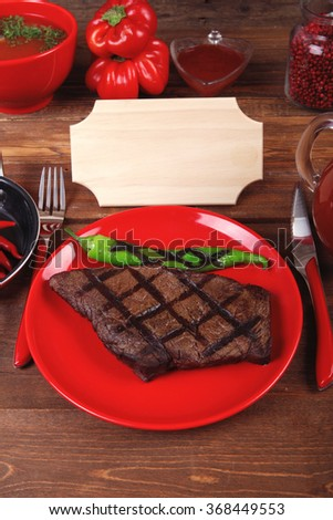 red theme lunch : fresh grilled bbq roast beef steak red plate green chili tomato soup ketchup sauce paprika glass ground pepper american peppercorn modern cutlery served wooden table empty nameplate - stock photo
