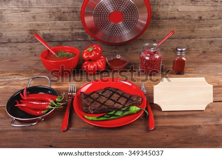 red theme lunch : grilled bbq roast beef steak red plate green chili tomato soup ketchup sauce paprika small glass ground pepper american peppercorn modern cutlery served wooden table empty nameplate - stock photo