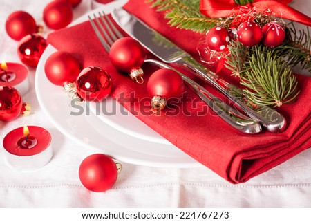 Red themed Christmas place setting with a colorful red napkin on white plates decorated with small red Xmas baubles and burning tea lights for a festive seasonal table - stock photo