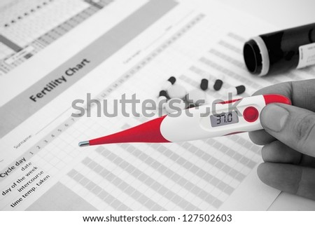 Red thermometer on black and white fertility composition - stock photo