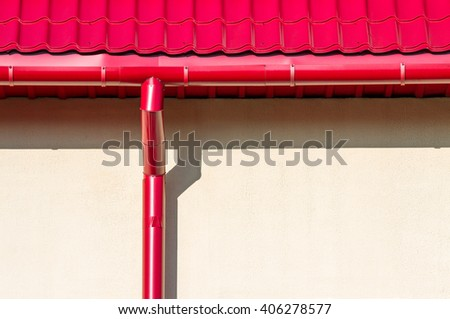 red tiled roof with new rain water downspout against wall - stock photo
