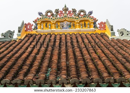 Red tiled roofs of the Giac Lam Pagoda in Ho Chi Minh City, Vietnam. Traditional pagoda decorated Vietnam with sculpture statue and red tiles. - stock photo