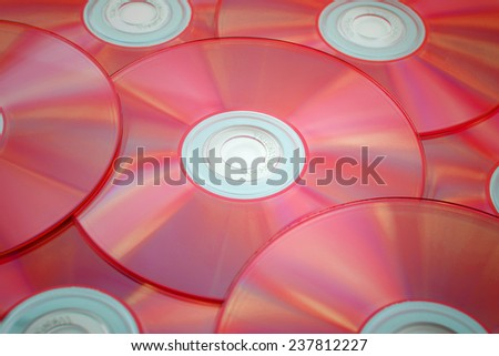 red tinted close-up of a stack of cd-roms - stock photo