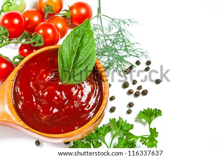 Red tomato sauce in a wooden spoon and ingredients, isolated in white - stock photo