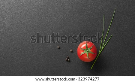 red tomato with green onion on black. Header for website - stock photo