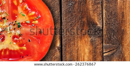 Red tomato with herbs on weathered wood background - stock photo