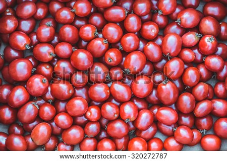 Red tomatoes at open air market. Group of ripe tomatoes forming a background. - stock photo