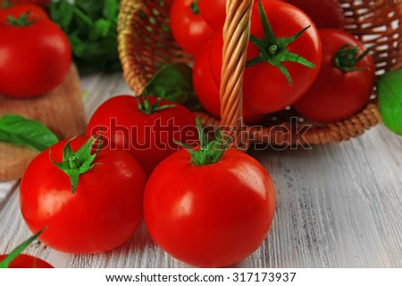 Red tomatoes in basket on wooden background - stock photo
