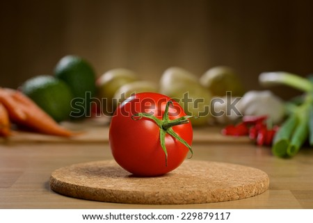 Red tomatoes on the wooden table with different vegetables on the background - stock photo