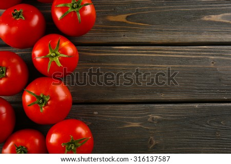 Red tomatoes on wooden background - stock photo