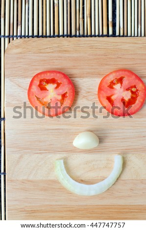 Red tomatoes slices and Onion slice on chopping board in smiling shape - stock photo