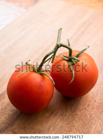 Red tomatoes with wooden chopping board background - stock photo