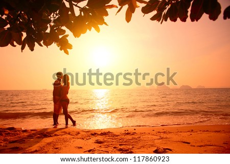 Red toned picture of a couple on a tropical beach at sunset - stock photo