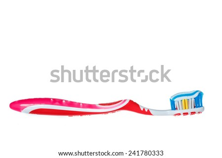 Red toothbrush with blue two color toothpaste on light surface. Photo of dental hygiene and health maintenance. Object isolated on white background without shadows - stock photo
