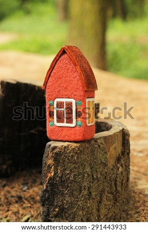 red toy house on the stub in the forest  - stock photo