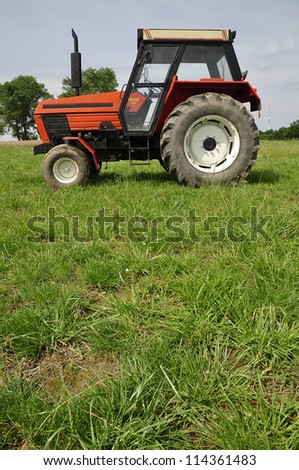 Red tractor on the meadow - stock photo