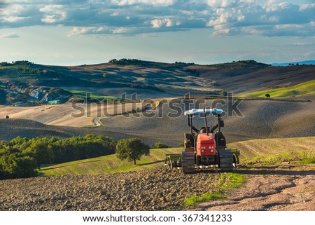 Red tractor on tracks in the landscape of Tuscany and cloudy skies - stock photo