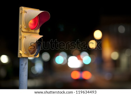 Red traffic light at night with city lights in background - stock photo