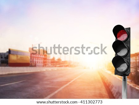 Red traffic light on the expressway asphalt road with car in a city landscape at sunrise. light sign for car stop and speed reduction. Dangerous,warning signal,semaphore driving. Driving on a Highway. - stock photo