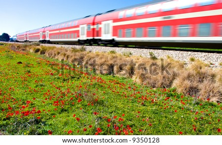 Red train moving fast in a field - stock photo