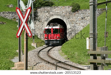 Red train out of train tunnel in Swiss, beautiful green grass - stock photo