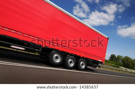 Red truck, lorry driving on country-road under blue sky - stock photo