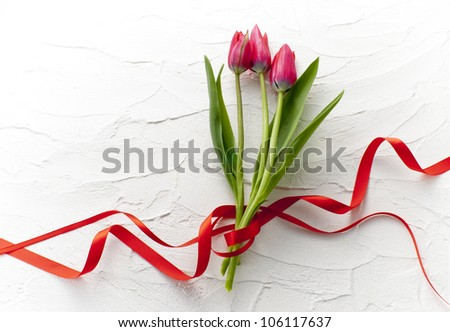 red tulip bouquet on white wall - stock photo