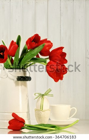 Red tulips and egg with bow on table - stock photo
