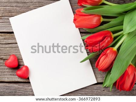 Red tulips, blank greeting card and candy hearts over wooden table. Valentines day background. Top view with copy space - stock photo