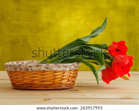 Red tulips in wicker basket - stock photo