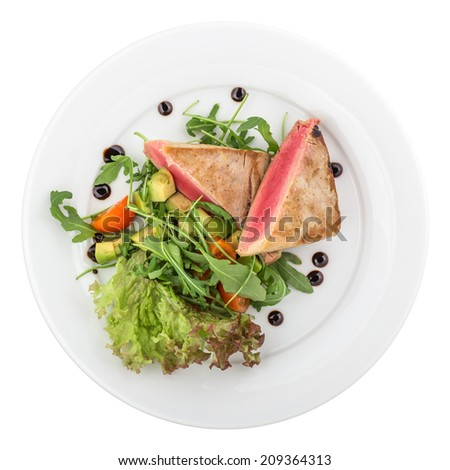 Red tuna steak garnished with avocado, arugula and tomatoes isolated on white background. Clipping path - stock photo