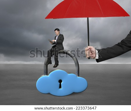red umbrella protect businessman using tablet on cloud lock with gray cloudy background - stock photo