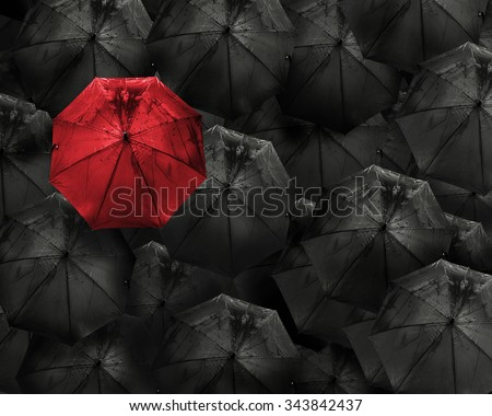 Red umbrella with water drop stand out from the crowd of many black umbrellas above view Business and leader concept - stock photo