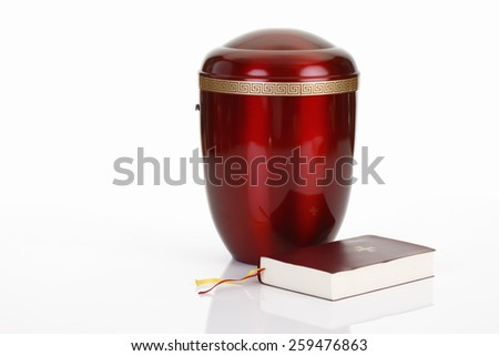 Red urn and bible on white background - stock photo
