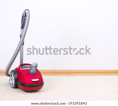 Red vacuum cleaner in empty room. - stock photo