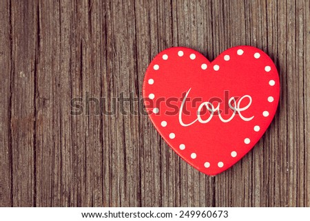 Red valentine's day holiday heart  on retro wooden background with vintage instagram toning - stock photo