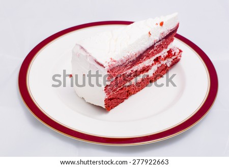 Red velvet cake is very dramatic looking with its bright red color sharply contrasted by a white cream - stock photo