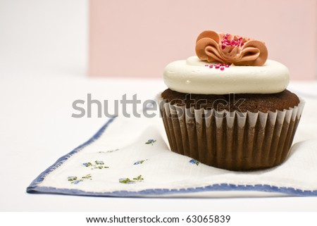 Red Velvet Cupcake decorated with white and pink frosting. - stock photo