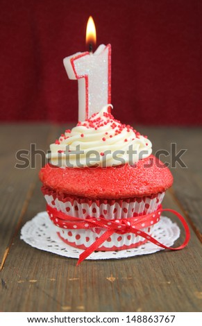 Red velvet cupcake with a number one candle on it - stock photo